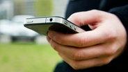 Die Hand eines Mannes hält ein Smartphone © picture alliance / dpa Themendienst Fotograf:  Franziska Gabbert