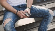 Das Bild zeigt einen jungen Mann, der ein Smartphone benutzt. © Imago / Westend61 Fotograf: Westend61