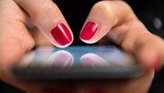 Nahaufnahme von zwei weiblichen Händen, die ein Smartphone umschließen und darauf tippen. © picture alliance / Sebastian Gollnow/dpa Foto: Sebastian Gollnow