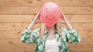 Das Bild zeigt eine Frau mit Lufballon vor dem Gesicht. © imago/westend61 Fotograf: Westend61