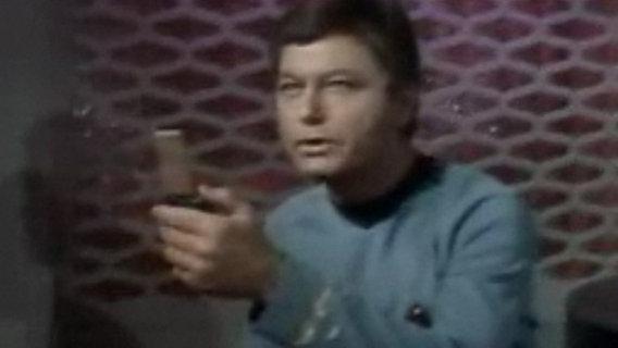 Das Bild zeigt Pille mit einem Kommunikator aus der Serie Star Trek. © CBS Entertainment