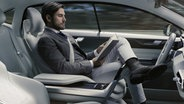 Volvo-Auto von Morgen: Fahrer sitzt hinter dem Lenkrad und ließt. © Volvo Car Group Fotograf: Volvo Car Group