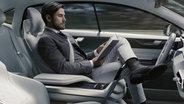 Fahrer sitzt hinter dem Lenkrad und ließt. © Volvo Car Group Fotograf: Volvo Car Group