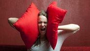 Frau schreit und hält sich zwei rote Kissen gegen die Ohren © picture alliance/chromorange Foto: CHROMORANGE / Bernd Juergens