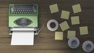 Eine grüne Schreibmaschine steht auf einem Tisch. © imago/Westend61 Fotograf: Westend61