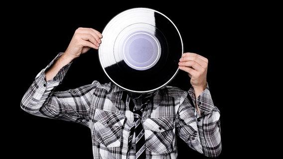 Ein Junge mit grauem Kapuzenpulli hält eine Schallplatte vor sein Gesicht. © Plainpicture Foto: Tabor Gus