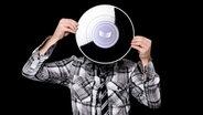 NDR Info Podcast: Ein Junge mit grauem Kapuzenpulli hält eine Schallplatte vor sein Gesicht. © Plainpicture Foto: Tabor Gus