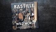 """Das CD-Cover des Albums """"Wild World"""" von Bastille zeigtzwei Männer, die auf einem Fenstersims sitzen und auf New York herunter blicken. Darüber sind der Bandname und der Titel des Albums zu sehen. © UMI / Virgin"""