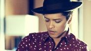 Porträtfoto des Sängers Bruno Mars mit Hut und gepunktetem Hemd. Weichgezeichnet. © Warner Music Fotograf: James Mooney