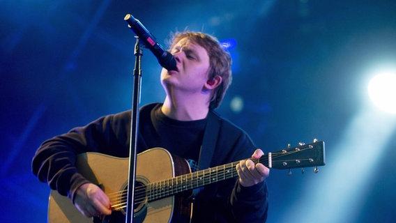 Lewis Capaldi spielt Gitarre auf einer Bühne. © picture alliance / Photoshot