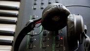 Ein paar schwarze Kopfhörer liegt auf einem Keyboard © dpa - Report Foto: Maximilian Schönherr