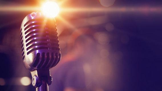 Ein Mikrofon im Gegenlicht. © fotolia Foto: vectorfusionart