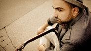 Der Musiker Fayzen mit einer Gitarre