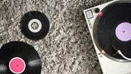 Ein Retro-Plattenspieler und zwei Schallplatten liegen auf einem Teppich. © complize / photocase.de Fotograf: complize / photocase.de