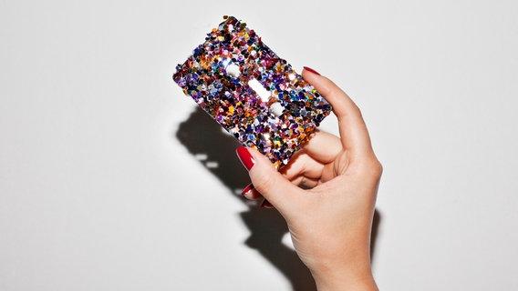 Zu sehen ist eine Hand, die eine glitzernde Kassette hält. © Nadine Platzek / photocase.de Foto: Nadine Platzek