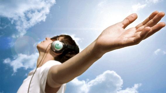 Junger Typ vor blauem Himmel mit Kopfhörern genießt die Musik © fotolia.com/Alexey Klementiev