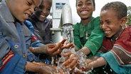 Kinder spielen mit Wasser an einer Pumpstation in Äthiopien © dpa