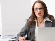 Junge Frau guckt grimmig über Bildschirm © Bildagentur-online