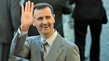 Bassar al-Assad hebt grüßend die Hand