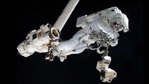 Ein Astronaut schwebt in einem weißen Raumanzug im All.