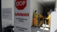 Mitarbeiter in Schutzanzügen stehen  in einer Isolierstation im Universitätsklinikum Eppendorf in Hamburg. © dpa Bildfunk