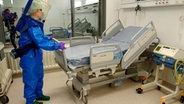 Ein Mann im Schutzanzug stellt ein Krankenbett ab im Behandlungszentrum für hochansteckende Erkrankungen am Universitätsklinikum Hamburg-Eppendorf. © picture alliance Fotograf: picture alliance / Hagen Hellwig