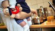 Eine Mutter kocht an einem Herd Mittagessen © dpa