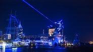 Das Bild zeigt ein Bild des blau erleuchteten Hamburger Hafens. © picture alliance / Daniel Reinhardt/dpa Foto: Daniel Reinhardt