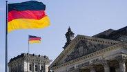 Das Bild zeigt eine deutsche Flagge und das Reichstagsgebäude © imago Fotograf: Westend61