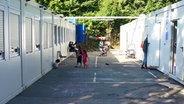 Zwischen zwei Containerreihen spielen Kinder. © n-joy Fotograf: Antje Barthold