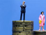 Ein Symbolbild zeigt einen Mann und eine Frau auf ungleich hohen Geldstapeln © imago stock&people