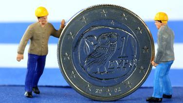 Zwei Miniaturfiguren stehen neben einer griechischen Euromünze © dpa