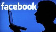 Ein Schatten vor dem Facebook-Logo. © dpa Foto: Julian Stratenschulte