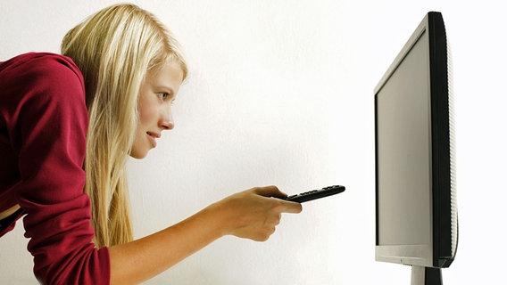 Junge blonde Frau schaltet mit der Fernbedienung einen Flachbildschirm ein © Peter Atkins/Fotolia.com