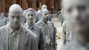 """Ganz in Grau: Menschen haben sich mit Lehm bedeckt und demonstrieren unter dem Motto """"1.000 Gestalten"""" in Hamburg. © picture alliance / Daniel Reinhardt/dpa Fotograf: Daniel Reinhardt"""