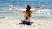 Eine Frau im Bikini am Strand © imago stock&people