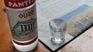 Eine Flasche Ouzo und ein Glas © dpa
