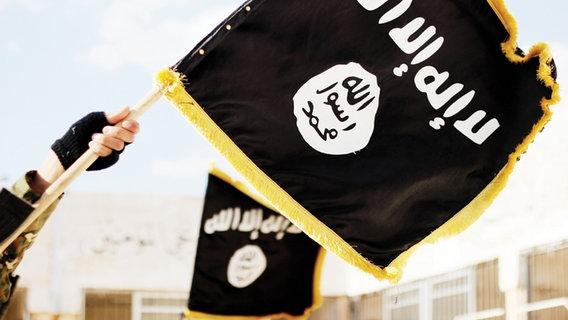 Eine Flagge des IS wird in die Luft gehalten. © picture alliance / ZUMA Press Foto: Dabiq