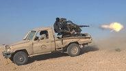 Ein Kämpfer des IS feuert sitzt mit einer Waffe auf einem Geländewagen. © picture alliance / ZUMA Press Fotograf: Handout