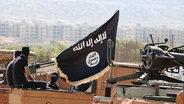 Das Bild zeigt maskierte Mitglieder der Terrormiliz Islamischer Staat in Syrien. © picture alliance / ZUMA Press Fotograf: Dabiq