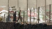 Eine Familie geht zwischen einem Zaun und der Mauer entlang. © NDR Foto: Simon Kremer