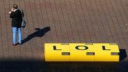 """Ein Mann steht am 10.10.2013 auf der Buchmesse in Frankfurt am Main (Hessen) neben einem großen """"LOL""""-Schriftzug. Die Abkürzung """"lol"""" steht für laughing out loud, (engl. laut lachen) © picture-alliance Fotograf: Daniel Reinhardt/dpa"""