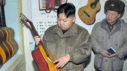 Kim Jong Un betrachtet eine Gitarre ©  picture alliance / Yonhap