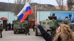 Eine Frau schwenkt in Balaklava eine russische Fahne. Im Hintergrund sind Soldaten zu sehen. © dpa Fotograf:  ITAR-TASS / Alexei Pavlishak)