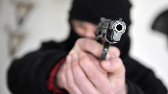Maskierter Mann zielt mit ausgestreckter Waffe © dpa - Report