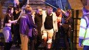 Einer verletzten Person wird am 22.05.2017 in Manchester, Großbritannien, in der Nähe der Manchester Arena geholfen. © dpa - Bildfunk Fotograf:  Joel Goodman/London News Pictures via ZUMA/dpa