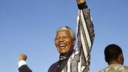 Nelson Mandela streckt seine linke Faust in die Luft und lächelt. © imago/Africa Media Online