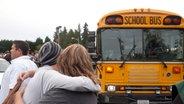Ein Schüler und seine Mutter halten sich im Arm und blicken in die Richtung eines Schulbuses. © dpa Fotograf: picture alliance/ Matt Mills Mcknight