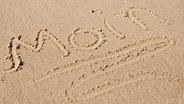 Das Wort moin geschrieben im Sand am Strand © Fotolia.com Foto: O.K.