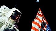 Harrison H. Schmitt steht neben der amerikanischen Flagge auf dem Mond. © NASA